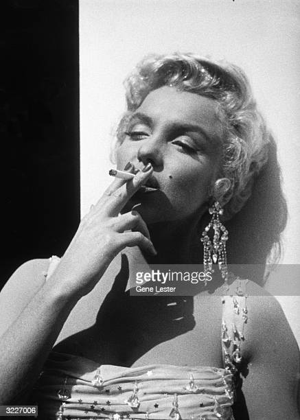 Portrait of American actor Marilyn Monroe in a white beaded gown leaning against a wall smoking a cigarette while on the 20th Century Fox studios set...