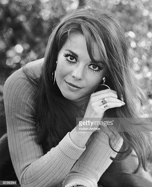Portrait of American actor Natalie Wood wearing false eyelashes and thick eyeliner with a ribbed turtleneck and hoop earrings posing outdoors