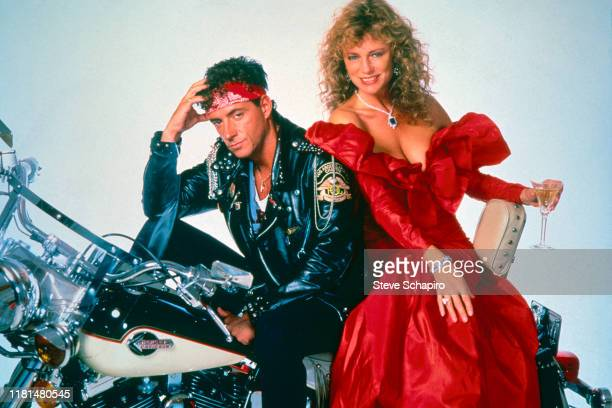 Portrait of American actor Ray Sharkey and English actress Jacqueline Bisset pose seated on a motorcycle and against a white background in costume...