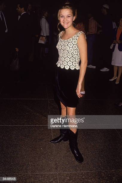 Portrait of American actor Reese Witherspoon wearing a black skirt and boots circa 1990s