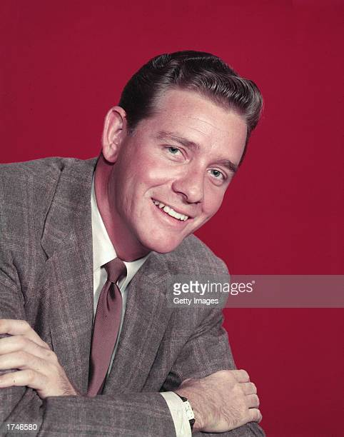 Portrait of American actor Richard Crenna wearing a suit, posing with arms crossed against a red background, 1950s.