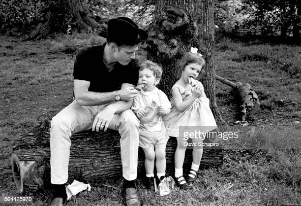 Portrait of American actor Robert Redford in a black hat and his children David and Shauna as they all sit on a log and eat ice cream in Central Park...