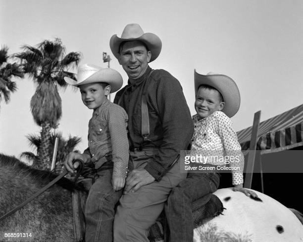 Portrait of American actor Slim Pickens as he sits along with two unidentified boys on an Appaloosa horse 1950s