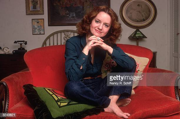 Portrait of American actor Swoosie Kurtz sitting on a red sofa with her legs crossed and her chin resting on her folded hands She wears jeans with...