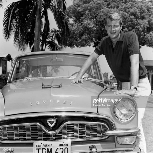 Portrait of American actor Troy Donahue leaning on the hood of a Toyota Toyopet car with a California license plate in front of a palm tree on a...