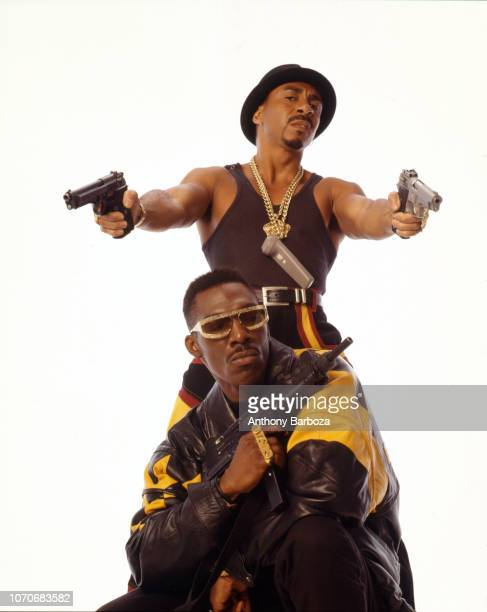 Portrait of American actor Tyrone Granderson Jones actor and comedian Charlie Murphy both in costume for the film 'CB4' as they pose against a white...