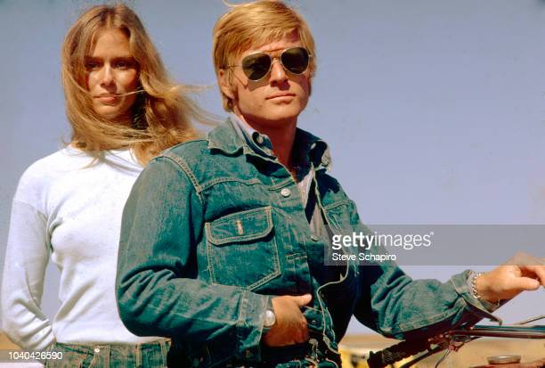 Portrait of American actors Lauren Hutton and Robert Redford the latter on a motorcycle as they pose on the set of the film 'Little Fauss and Big...