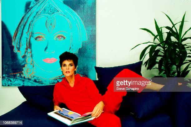 Portrait of American actress Ali MacGraw as she reclines on a sofa with a book in her hands, Los Angeles, California, 1982.