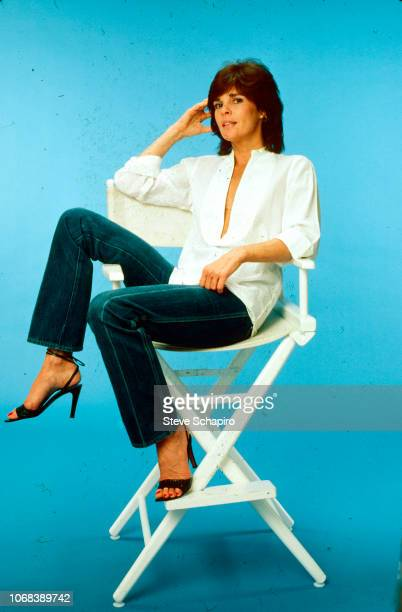 Portrait of American actress Ali MacGraw as she sits in a director's chair in front of a blue background Los Angeles California 1982