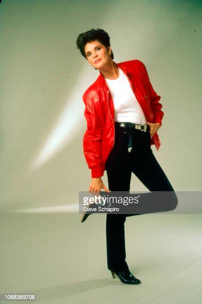 Portrait of American actress Ali MacGraw dressed in a red leather jacket as she poses with one hand in her pockets and the other holding the heel of...
