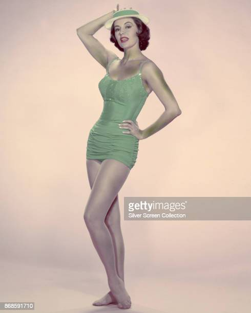 Portrait of American actress and dancer Cyd Charisse as she poses in a green swimsuit and hat 1950s