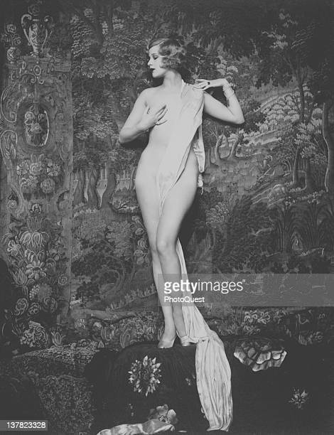 Portrait of American actress and entertainer Hazel Forbes as she poses naked except for jewelry heels and a strategically placed sash late 1920s