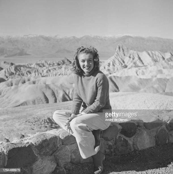 Portrait of American actress and model Marilyn Monroe as she sits on a low brick wall in Death Valley, California, 1945.