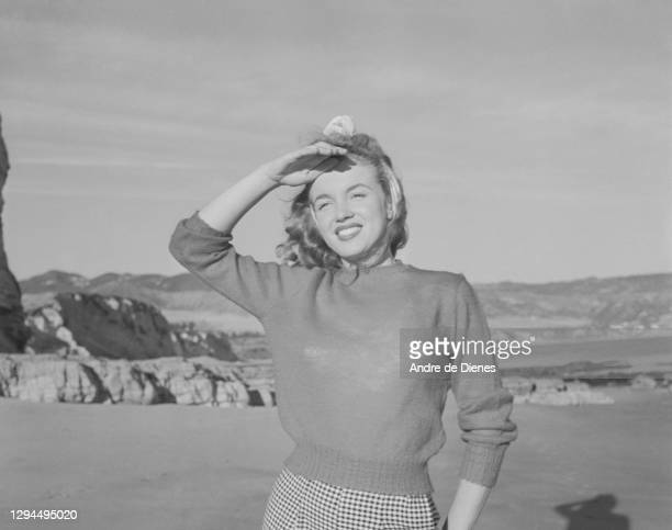 Portrait of American actress and model Marilyn Monroe in a sweater and checkered trousers, as she poses at Zuma Beach's Paradise Cove, California,...