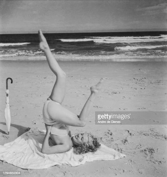 Portrait of American actress and model Marilyn Monroe , in a swimsuit, as she poses, lying on a blanket, on Long Island's Tobay Beach, Oyster Bay,...