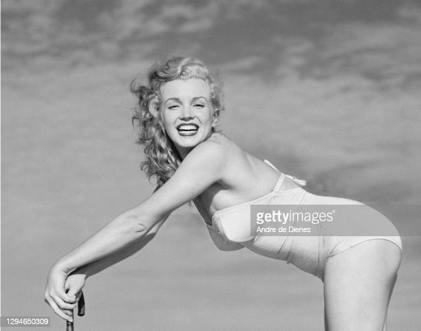 Portrait of American actress and model Marilyn Monroe , in a swimsuit, as she poses with an umbrella on Long Island's Tobay Beach, Oyster Bay, New...