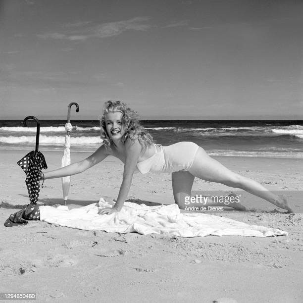 Portrait of American actress and model Marilyn Monroe , in a swimsuit, as she poses on a blanket, beside a pair of umbrellas, on Long Island's Tobay...