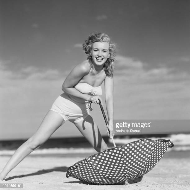 Portrait of American actress and model Marilyn Monroe , in a swimsuit, as she poses with a polka dot umbrella on Long Island's Tobay Beach, Oyster...