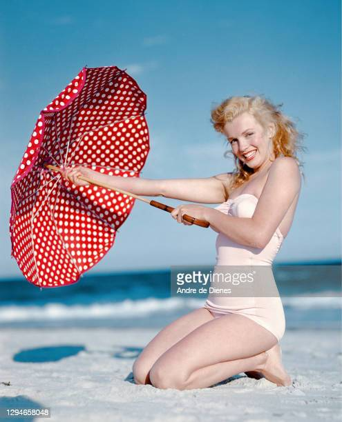 Portrait of American actress and model Marilyn Monroe , in a white swimsuit, as she poses with a red, polka dot umbrella on Long Island's Tobay...