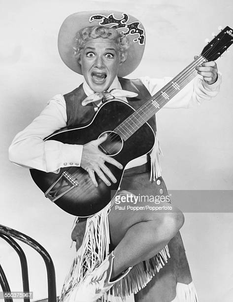 Portrait of American actress and singer Betty Hutton pictured wearing a cowgirl costume and holding an acoustic guitar circa 1950