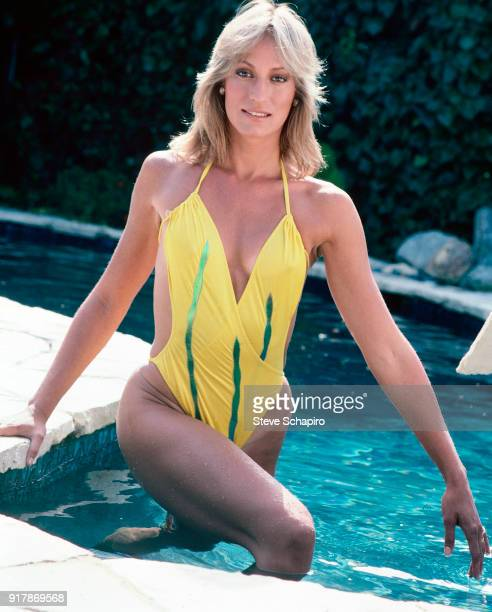 Portrait of American actress and stuntwoman Sandahl Bergman in a yellow swimsuit as she stands in swimming pool Los Angeles California 1980s
