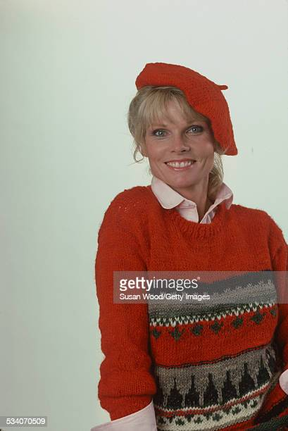 Portrait of American actress and television personality Cathy Lee Crosby as she poses in a red sweater and a beret July 1980