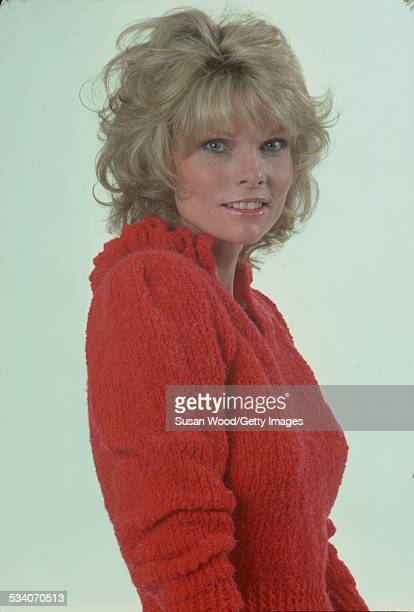 Portrait of American actress and television personality Cathy Lee Crosby as she poses in a red sweater and white trousers July 1980