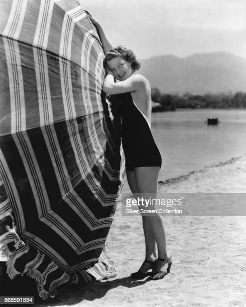 Portrait of American actress Ann Sheridan as she poses on the beach beside an opened umbrella late 1930s This image has been retouched