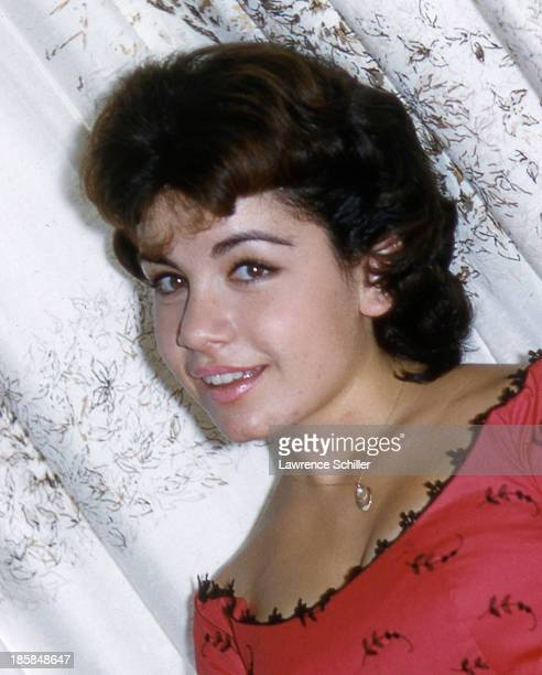 Portrait of American actress Annette Funicello in a red dress as she poses in front of a curtain in her home Los Angeles California 1959