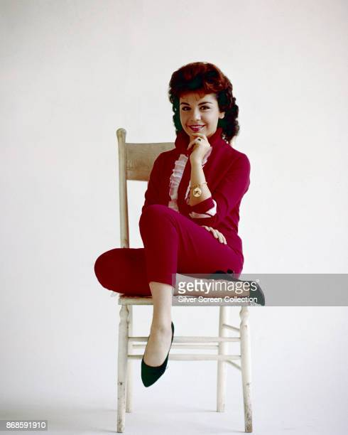 Portrait of American actress Annette Funicello in a red pantsuit with white ruffles as she sits in a chair one hand on her chin in front of a white...
