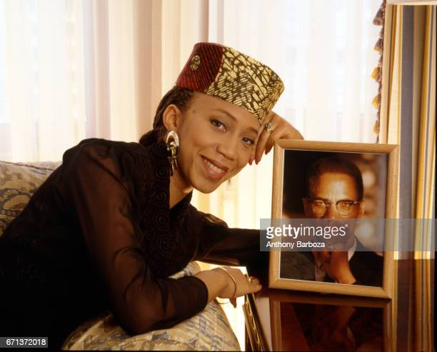 Portrait of American actress author and activist Attallah Shabazz as she poses with a framed portrait of her father minister and Civil Rights...