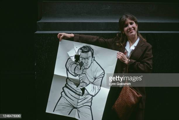 Portrait of American actress Carrie Fisher as she holds a target, complete with bullet holds, from a firing range, New York, 1979. She was taking...