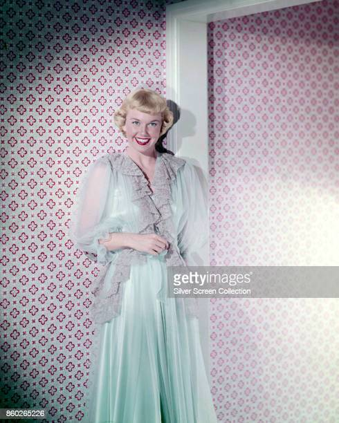 Portrait of American actress Doris Day in a pale turquiose peignoir as she leans against a wall and smiles broadly 1940s or early 1950s