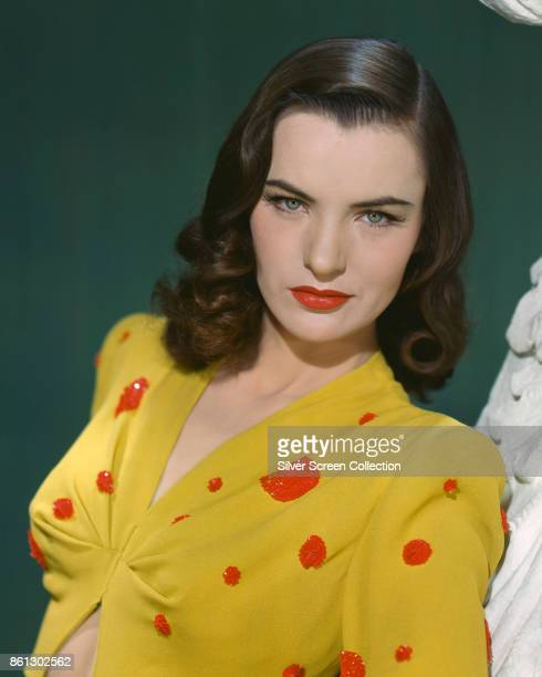 Portrait of American actress Ella Raines in a midriffbaring yellow top with red sequins as she poses against a green backdrop 1940s