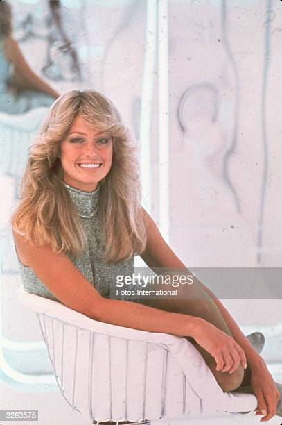 Portrait of American actress Farrah Fawcett dressed in a highnecked sleeveless outfit and curled up in a chair June 1977