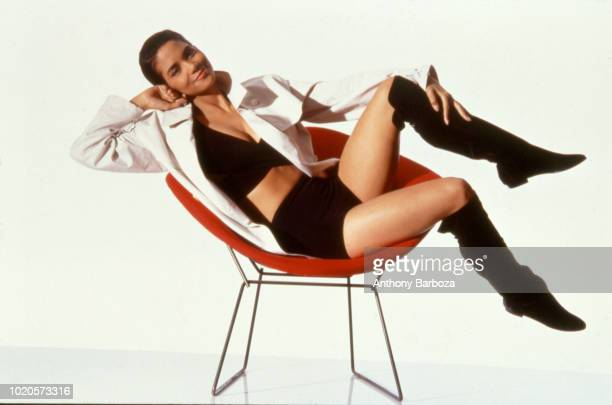 Portrait of American actress Halle Berry as she lounges in a chair in front of a white backgroud New York 1990s