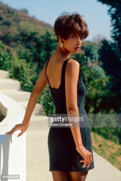 Portrait of American actress Halle Berry dressed in a black sleeveless minidress as she looks back over her shoulder Los Angeles California 1986