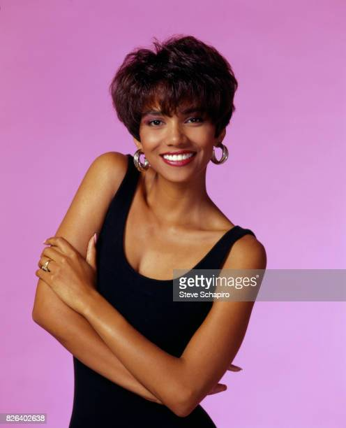 Portrait of American actress Halle Berry dressed in a black sleeveless dress as she poses with her arms crossed 1990s