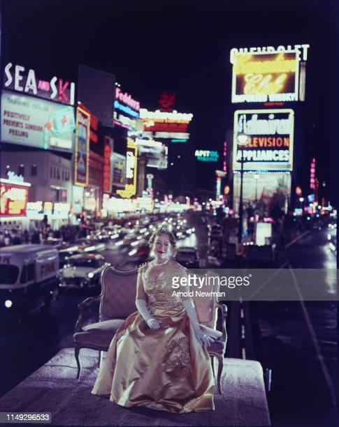 Portrait of American actress Helen Hayes dressed in an evening gown as she sits on a neoclassical loveseat and carpet atop a low building in Times...