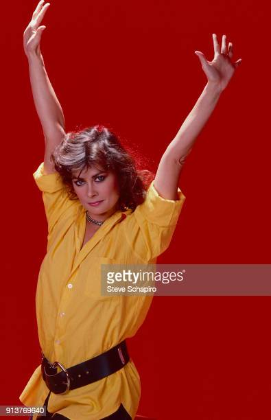 Portrait of American actress Jane Badler as she poses against a red background Los Angeles California 1984