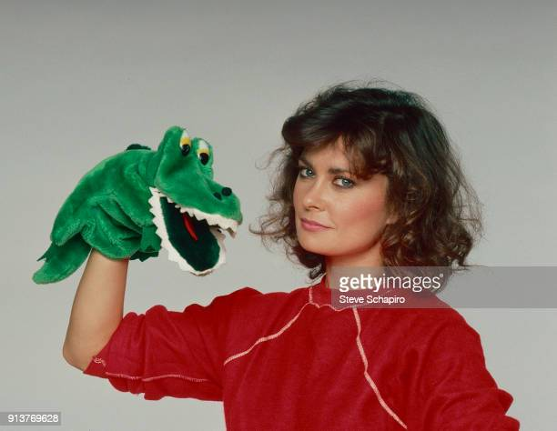 Portrait of American actress Jane Badler as she poses with an alligator hand puppet Los Angeles California 1984