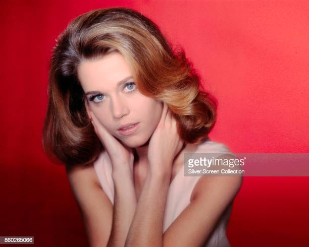 Portrait of American actress Jane Fonda as she poses against a red background late 1960s or early 1970s