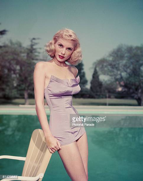 Portrait of American actress Janet Leigh as she leans against a patio chair and wears a purple bathing suit next to a large swimming pool 1950s