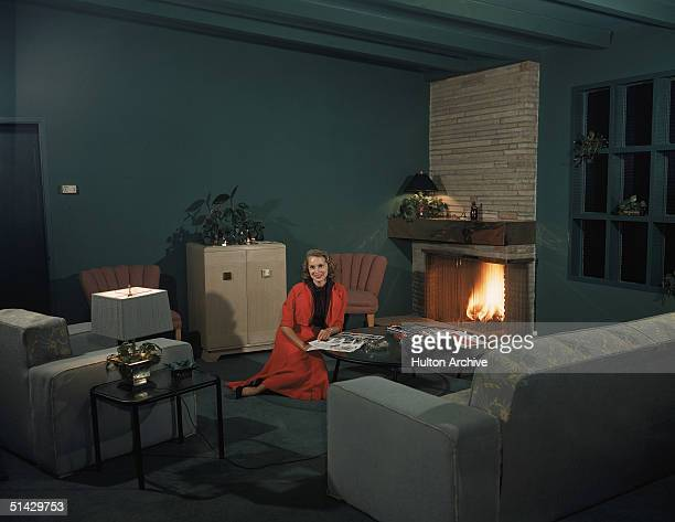 Portrait of American actress Janet Leigh as she sits on the floor of a green living room in a red skirt and jacket and reads a magazine at a coffee...