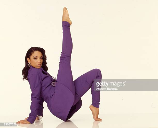 Portrait of American actress Jasmine Guy as she strikes a pose dressed in purple and barefoot against a white background 2000