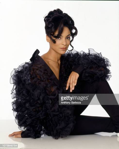 Portrait of American actress Jasmine Guy dressed in black as she poses on the floor against a white background 2000