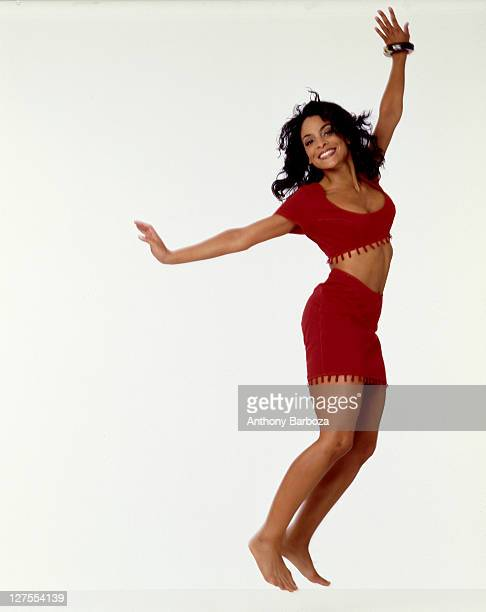 Portrait of American actress Jasmine Guy dressed in red as she jumps against a white background 1990s