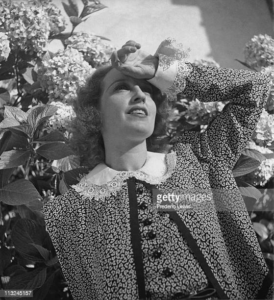 Portrait of American actress Jeanette MacDonald shading her eyes circa 1940