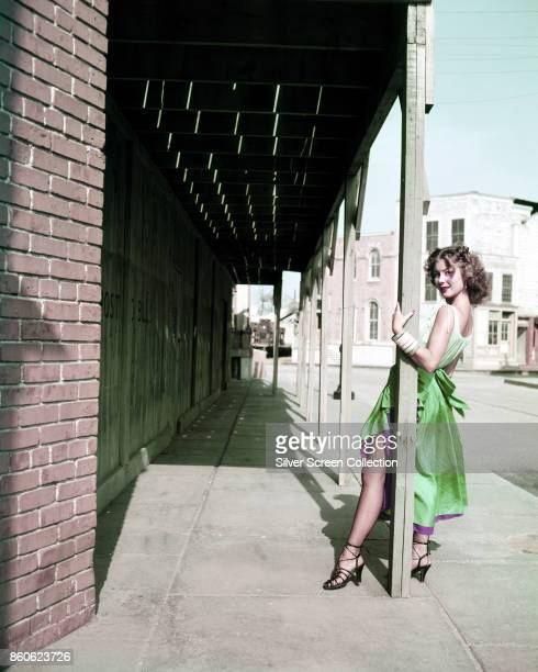 Portrait of American actress Jennifer Jones in a green dress with a purple underskirt as she holds onto a wooden porch support on a Western town set...
