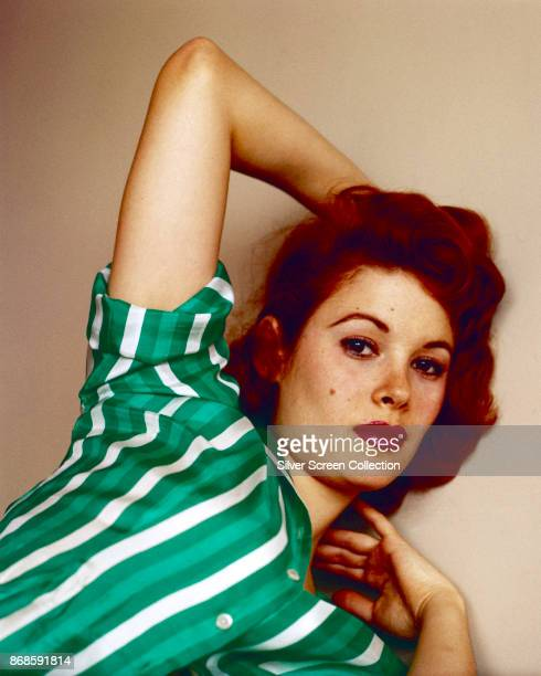 Portrait of American actress Jill St John in green and white striped blouse as she poses with one arm above her head 1960s